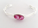 Beautiful Cerise wave bangle fully adjustable to fit the wearer handpainted in wax and sealed in glass