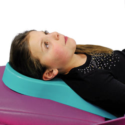A young dental patient rests on the teal foam airway positioner which supports her torso and helps maintain a chin up position  ・ Airway Positioner | Specialized Care Co