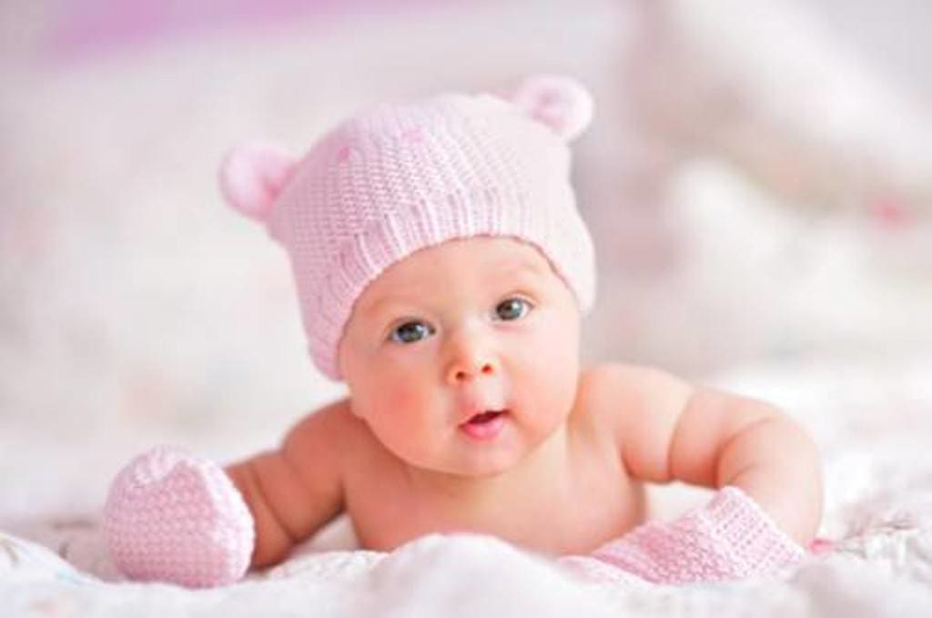 Infant in Pink Cap - The Palm Beach Baby