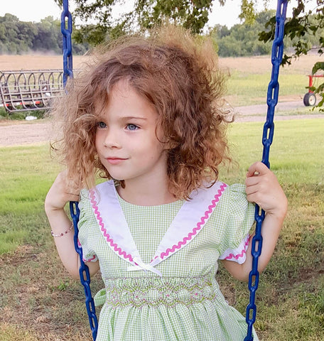 Ethically made Victoria dress from The Open Road on little girl on a swing with a breeze blowing through her curly hair