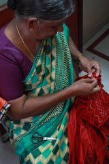 Indian lady hand-smocking the ethically made dresses on The Open Road