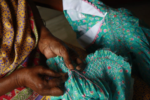 Hands of an Indian women artisan hand-smocking the ethically made dresses on The Open Road