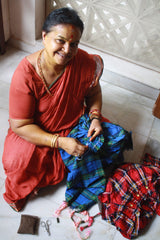Indian lady smiling at the camera while working on hand-smocking the ethically made dresses on The Open Road