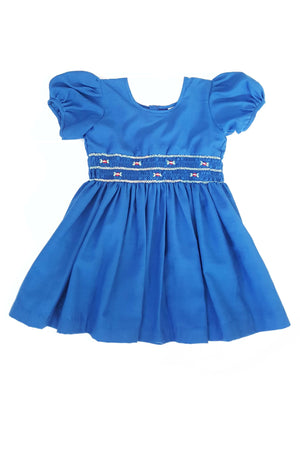 Front of ethically made royal blue short sleeve Cara dress featuring a hand-smocked bodice with elegant little red rosettes for contrast