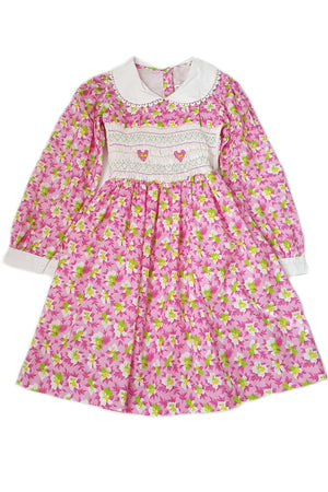 Bold pink floral print long sleeve dress with contrasting white peter pan collar, cuffs and white bodice featuring hand-smocked baskets of flowers for girls