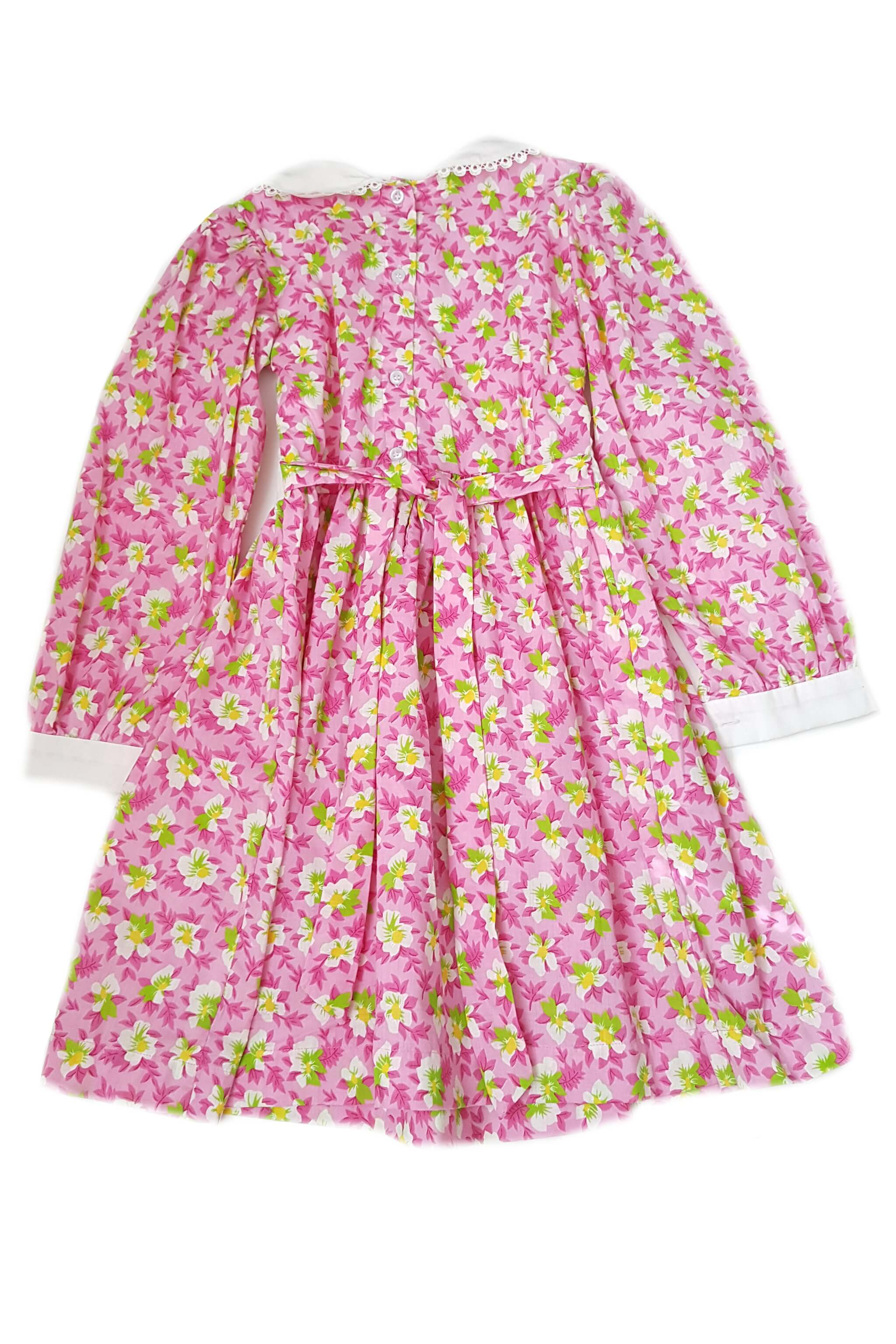 Back of bold pink floral print long sleeve dress with contrasting white peter pan collar, cuffs and white bodice featuring hand-smocked baskets of flowers with button back opening and sash for girls