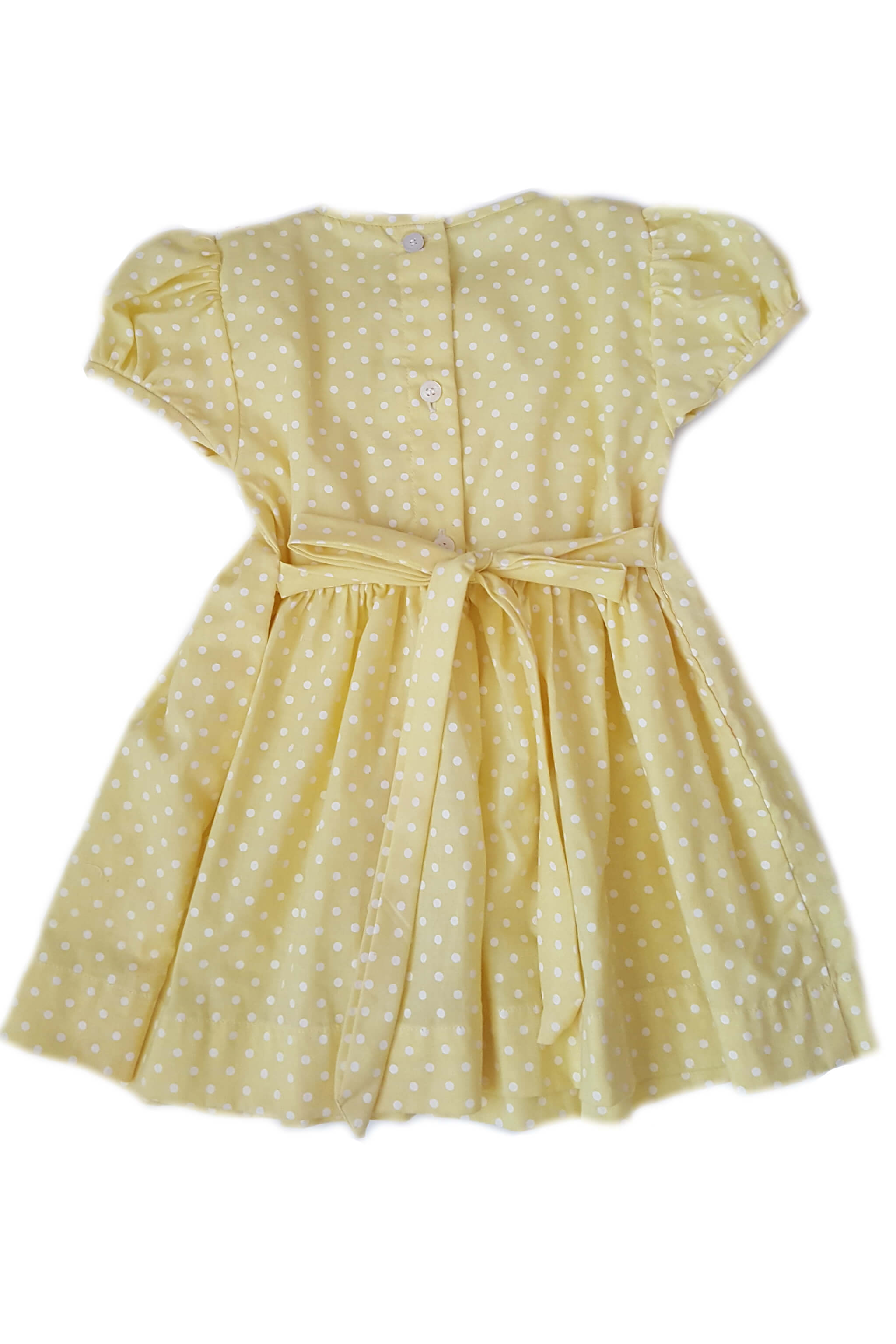 Back of yellow pin dot dress with hand-smocked bodice and white square collar with hand-embroidered orange rosettes with button back and sash for baby girls