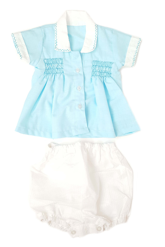 Front of blue shirt with delicate hand-smocked bodice and contrasting white collar and cuffs with white bloomer for baby boys