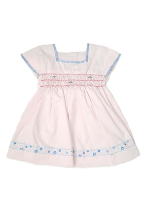 Blush pink dress features square neck with contrasting sky blue trim and on cap sleeves with hand-smocked bodice and sheer blue lace at the hem for baby girls