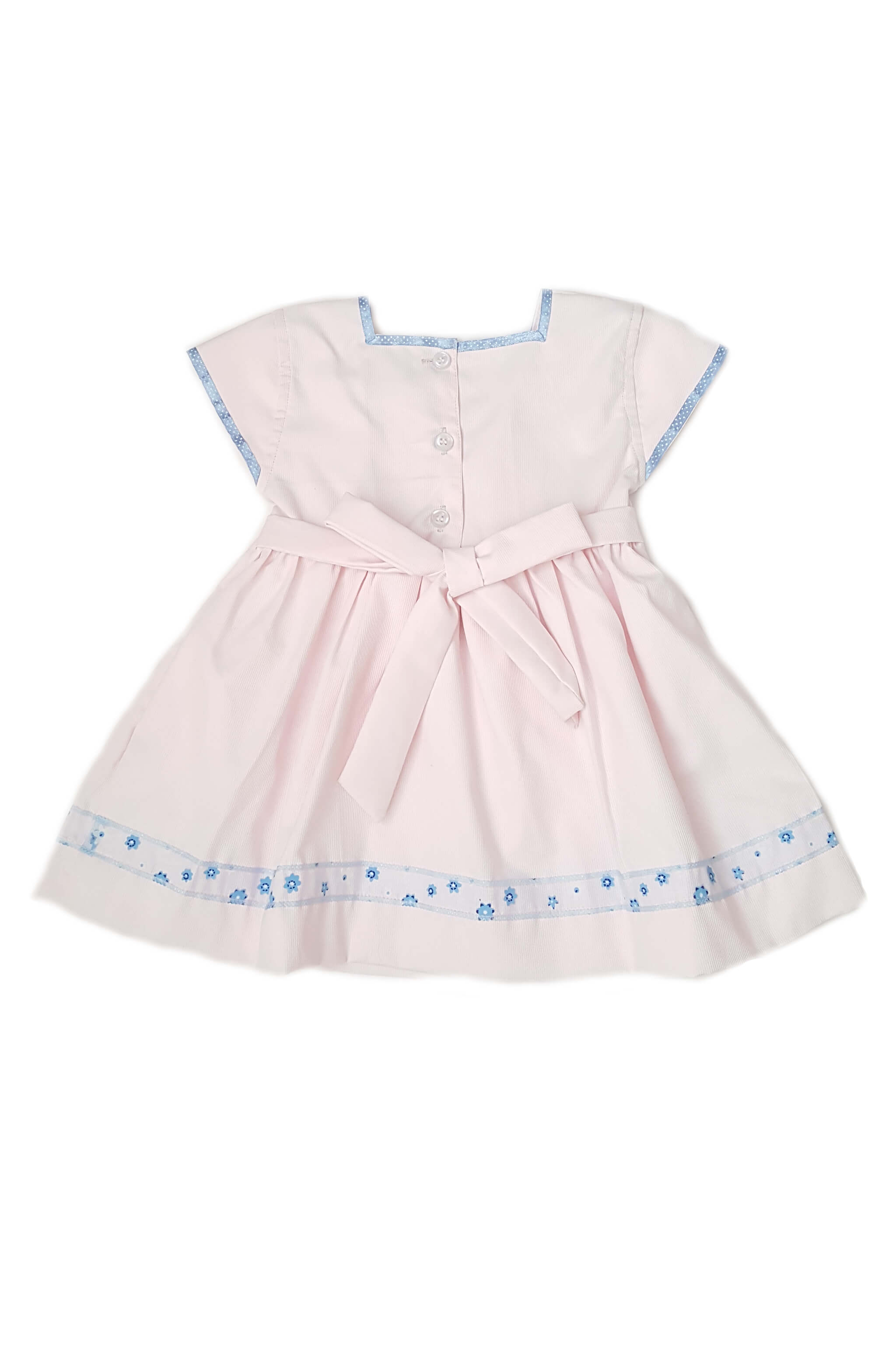 Back of blush pink dress features square neck with contrasting sky blue trim and on cap sleeves with hand-smocked bodice and sheer blue lace at the hem with button back and sash for baby girls