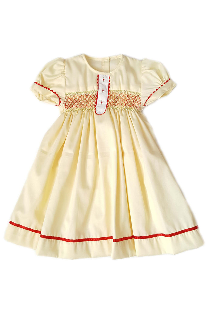 Buttercream yellow dress with white placket features red hand-embroidered rosettes and red hand-smocked bodice with red satin trim for girls