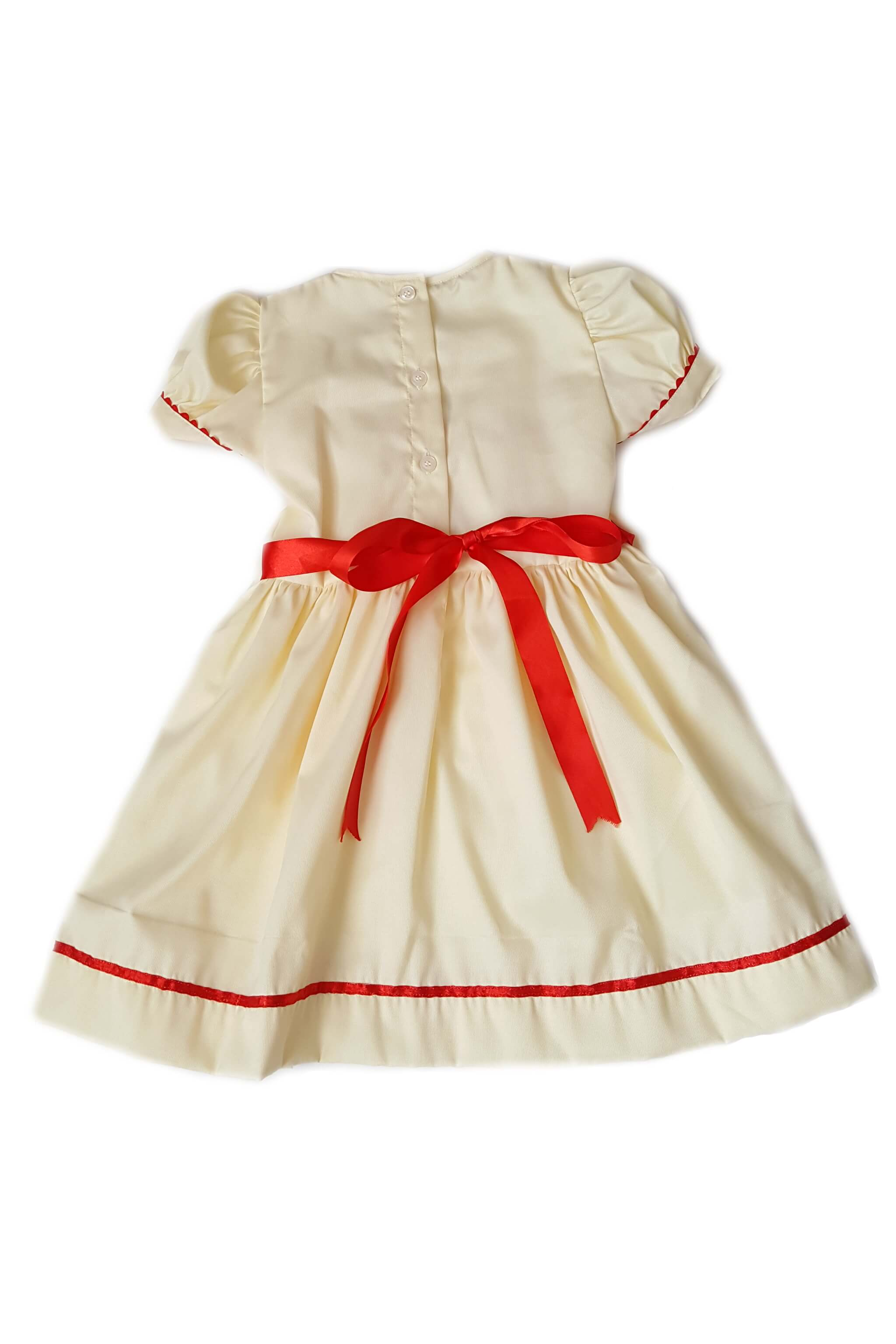 Back of buttercream yellow dress with white placket features red hand-embroidered rosettes and red hand-smocked bodice with red satin trim and sash for girls