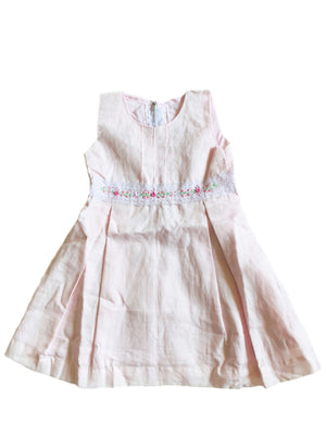 Pale pink box pleated dress with white lace trim at the bodice and pink hand-embroidered rosettes for girls