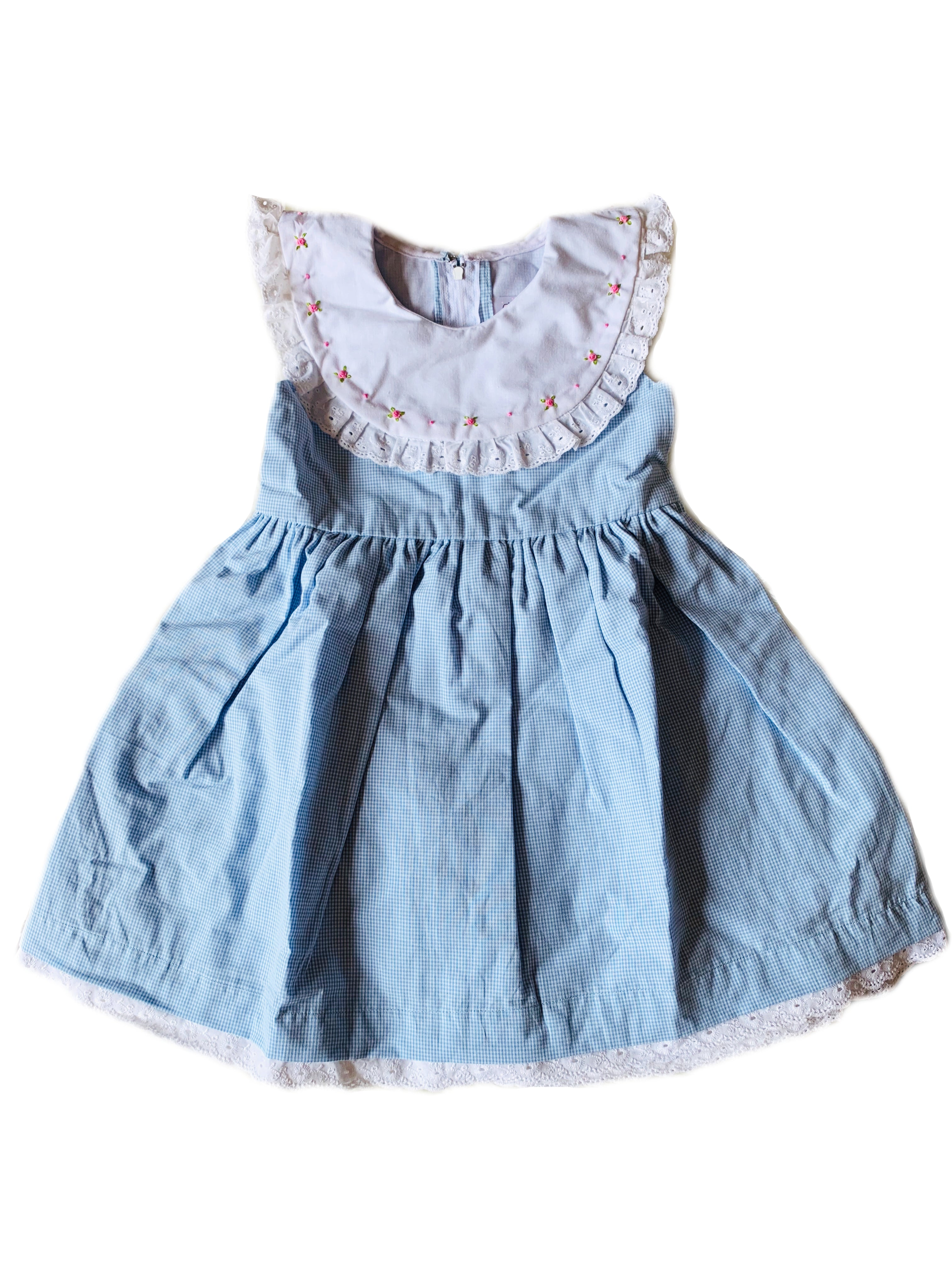 Baby blue gingham sleeveless dress with contrasting round white collar and dainty hand-embroidered flowers, lace to trim the hem and sash to tie at waist for girls