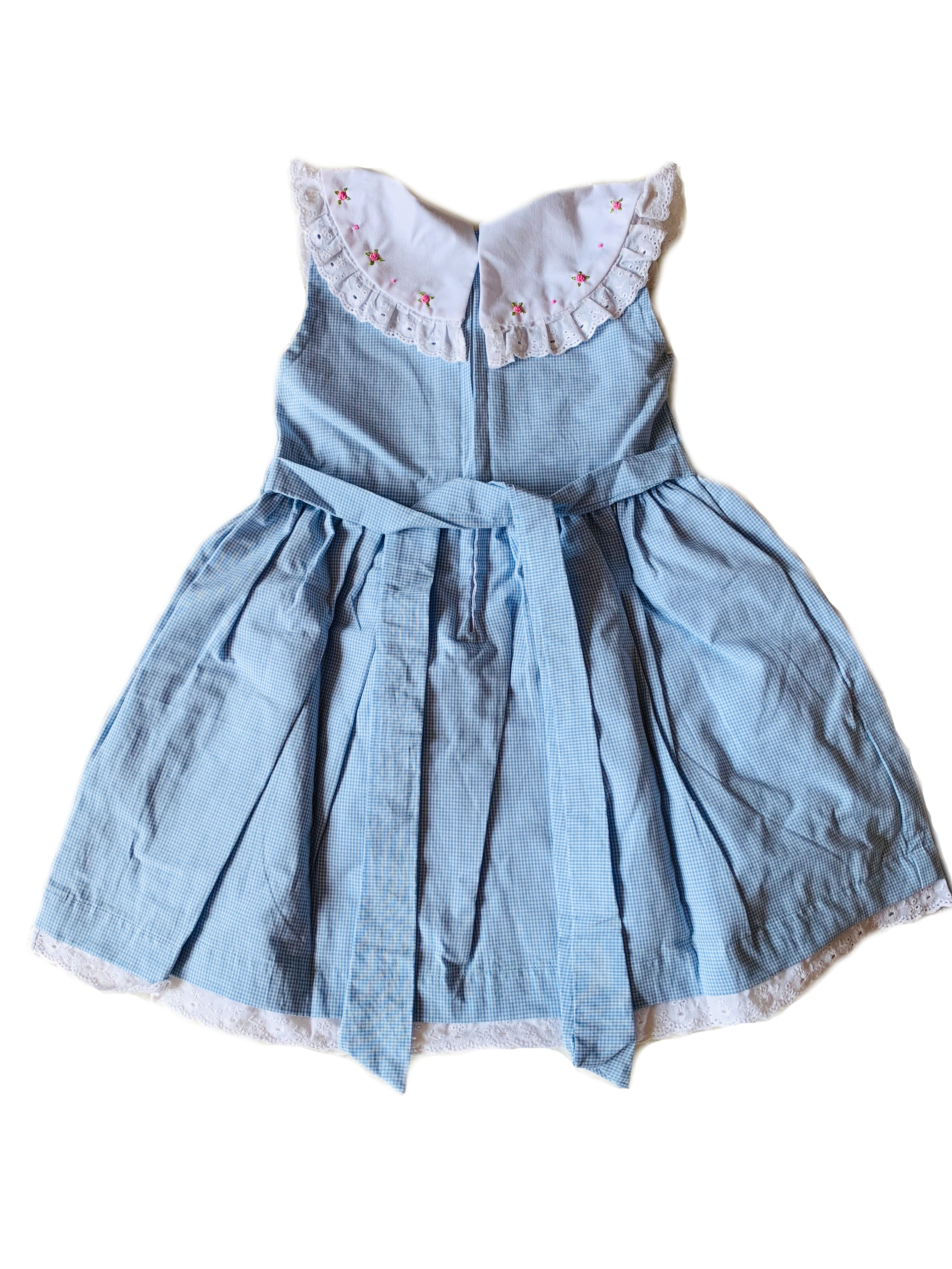 Back of baby blue gingham sleeveless dress with contrasting round white collar and dainty hand-embroidered flowers, lace to trim the hem, zippered back and sash to tie at waist for girls