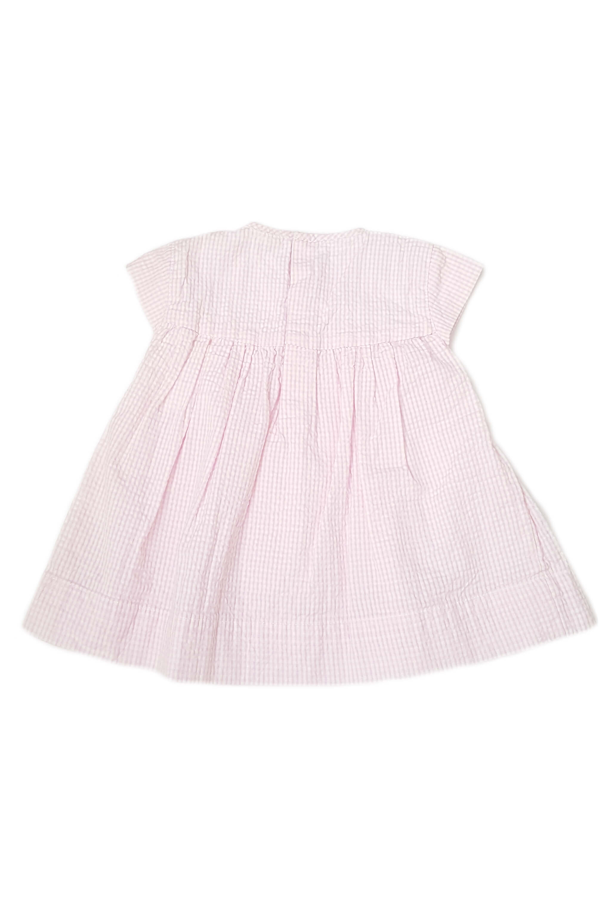 Back of classic pale pink seersucker dress with cap sleeves and hand-smocked bodice with snap fastening for baby girls