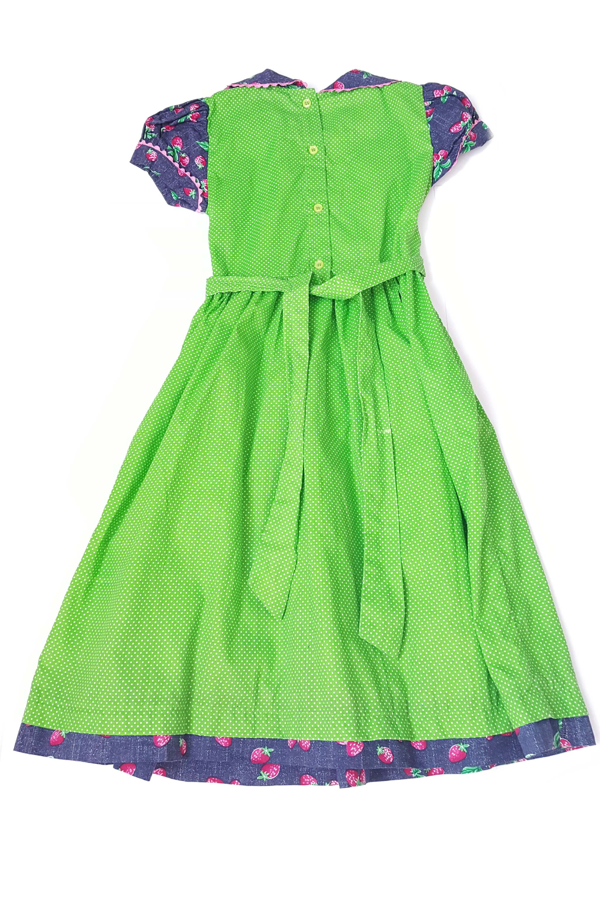 Back of short sleeved apple green pin dot Jade dress with contrasting strawberry print peter pan collar, and traditional hand-smocked bodice with button back and sash to tie at waist