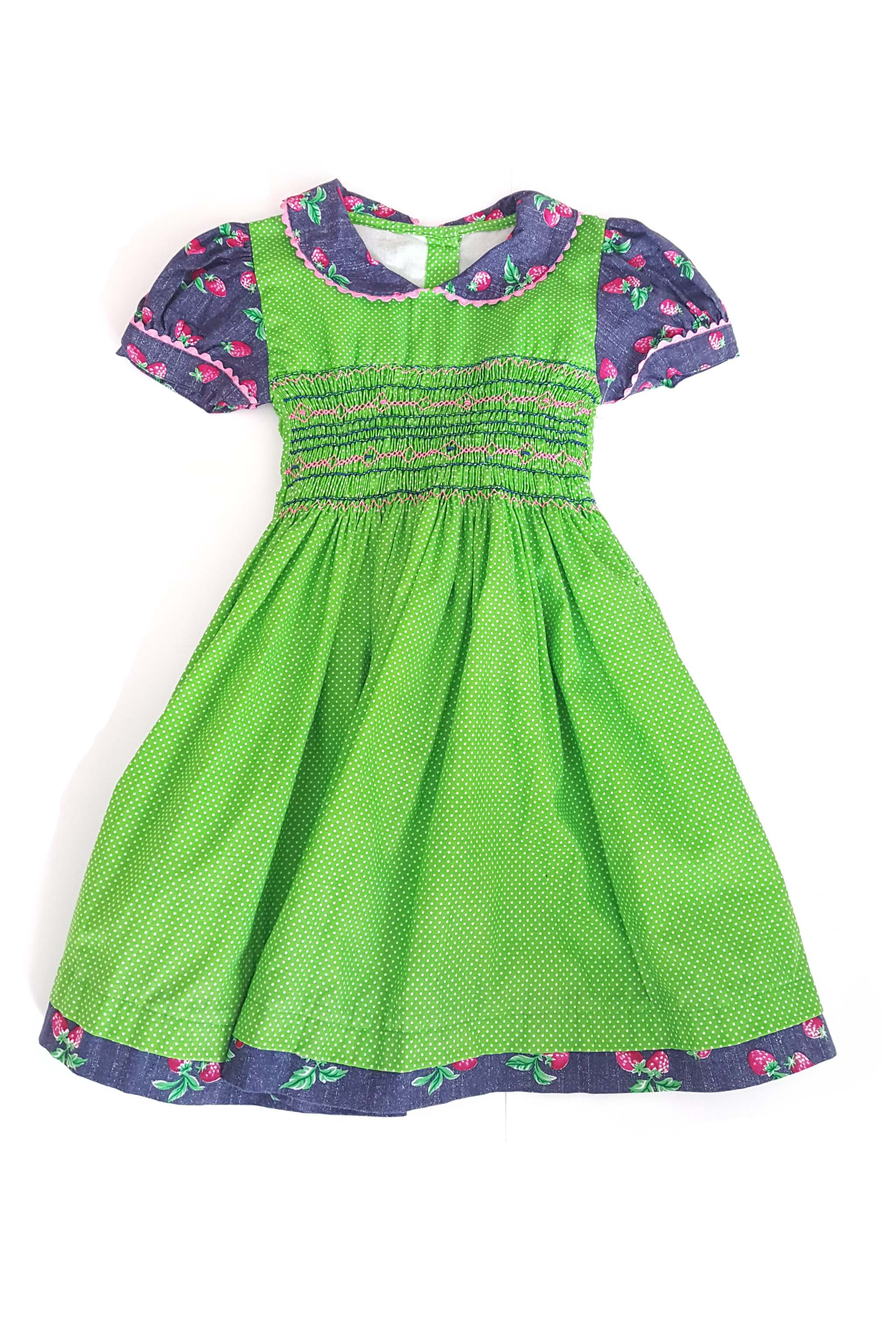 Front of short sleeved apple green pin dot Jade dress with contrasting strawberry print peter pan collar, and traditional hand-smocked bodice