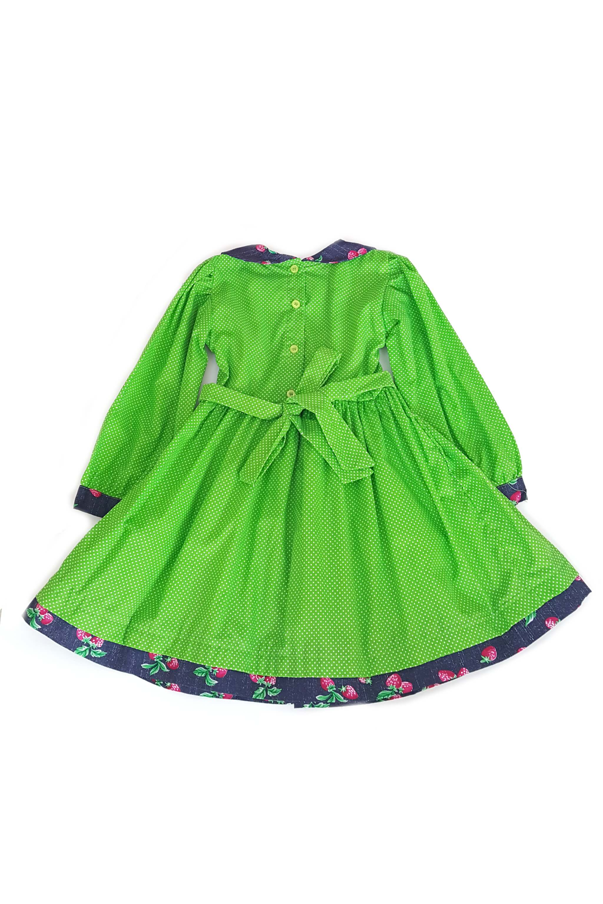 Back of long sleeved apple green pin dot Jade dress with contrasting strawberry print peter pan collar, and traditional hand-smocked bodice with button back and sash to tie at waist
