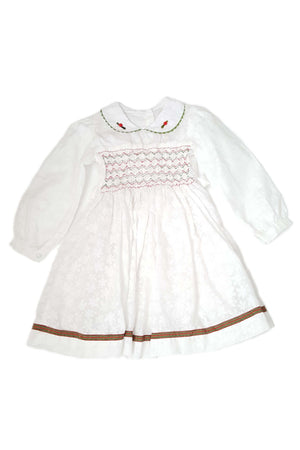Front of ethically made white little girls long sleeve dress with red and green hand-smocked bodice and peter pan collar with embroidery