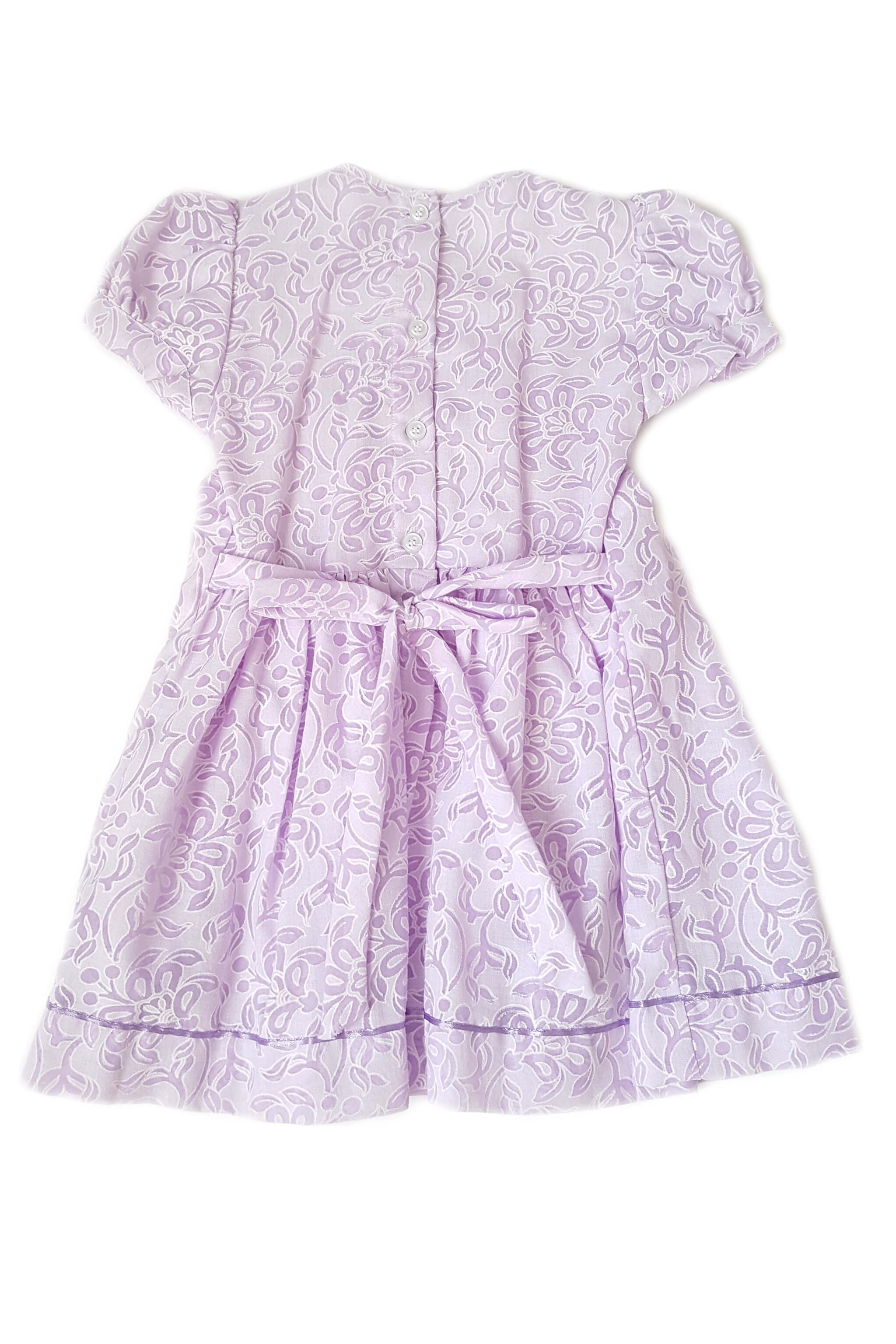 Back of lavender floral print dress with hand-smocked bodice and soft purple satin trim with button back and sash for girls