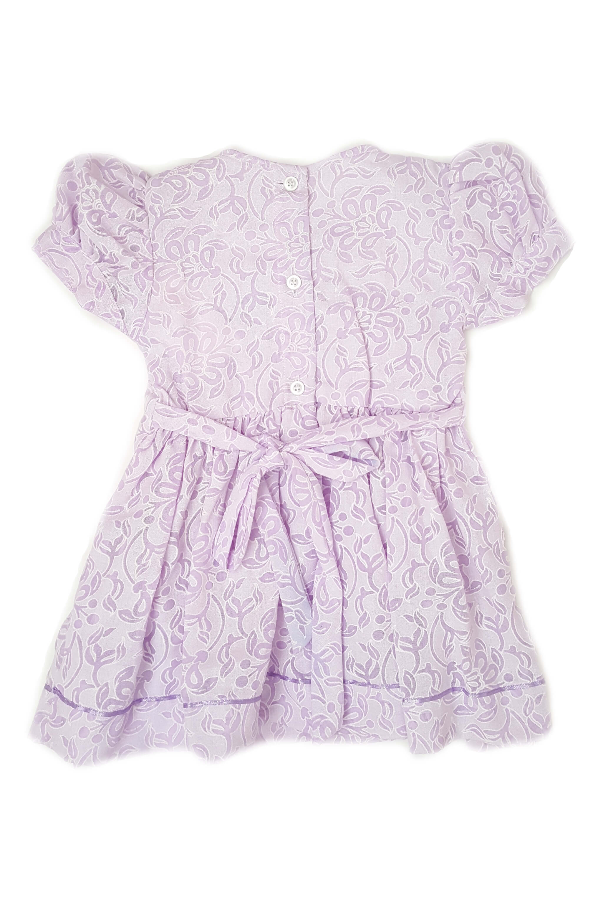 Back of lavender floral print dress with hand-smocked bodice and soft purple satin trim with button back and sash for baby girls