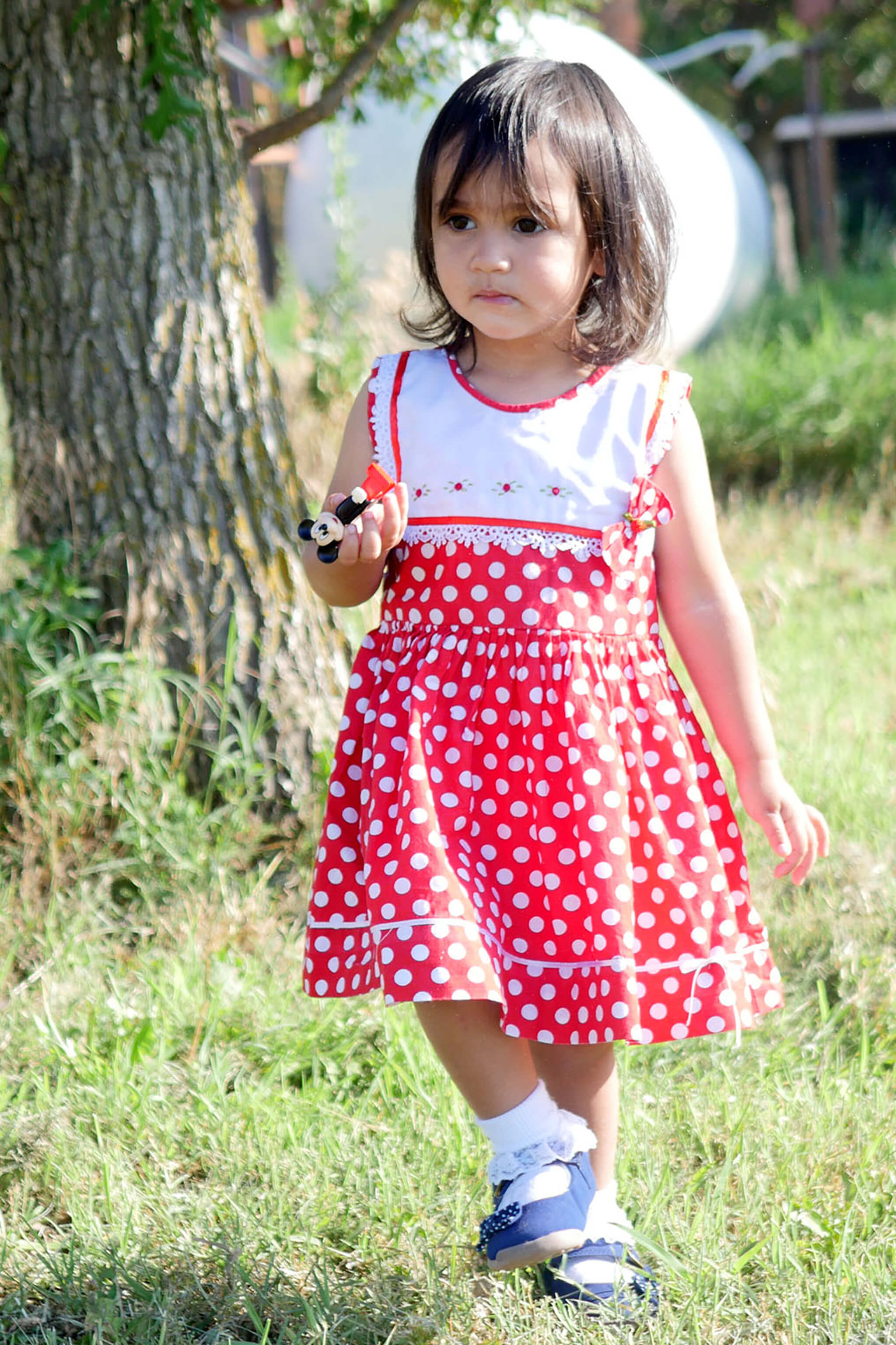 Little girl wearing the ethically made red polka dot Rosa dress in a garden
