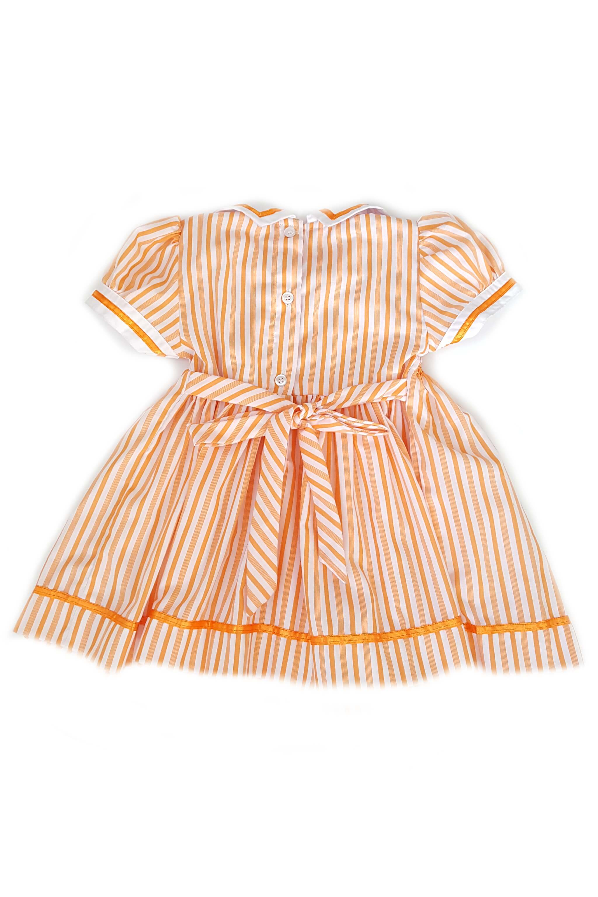 Back of pumpkin orange striped Pauline dress featuring a nautical white collar with orange trim and hand-smocked bodice with button back and sash to tie at the waist