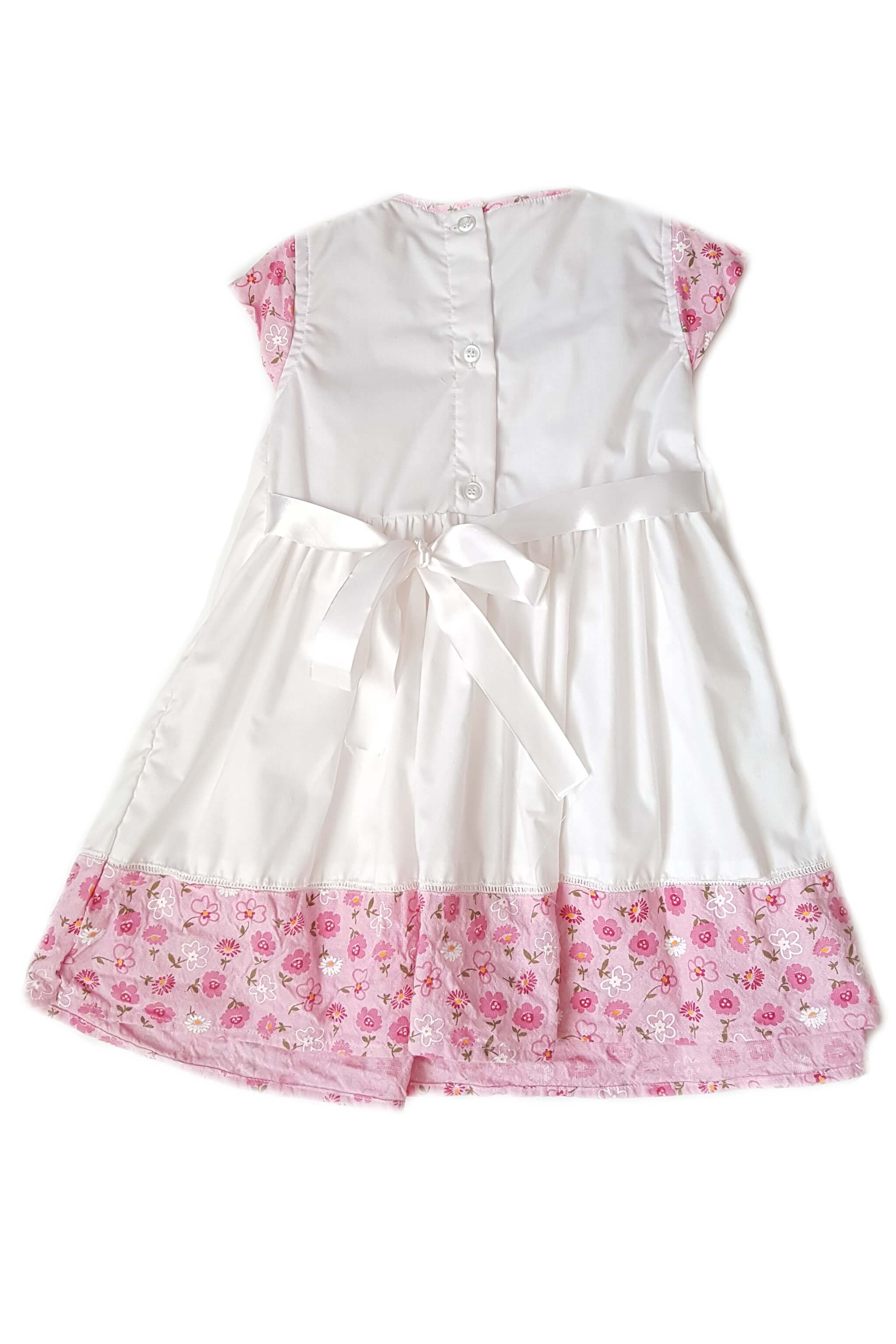 Back of white dress with hand-smocked chest and contrasting cap sleeves and hem with floral print and button back and white satin sash for girls