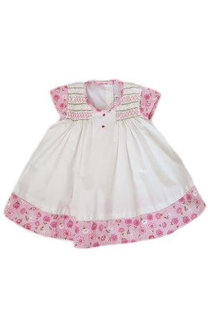 White dress with hand-smocked chest and contrasting cap sleeves and hem with floral print for baby girls