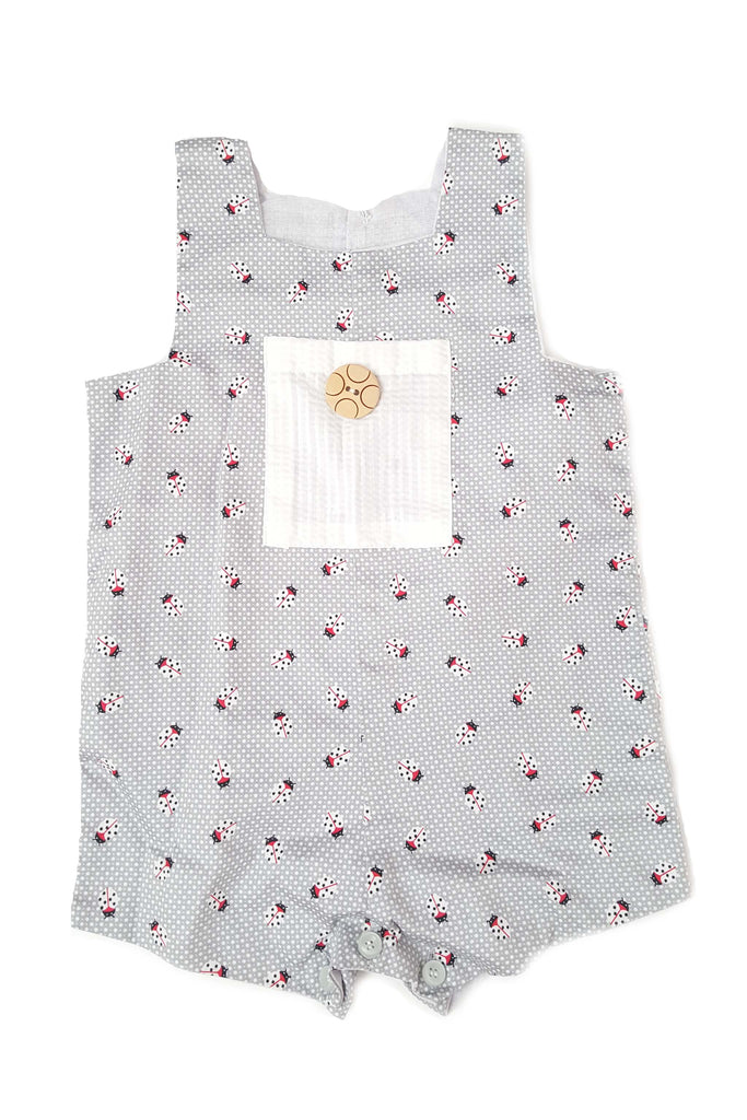 Grey romper with ladybug print and contrasting white seersucker front pocket for baby boys