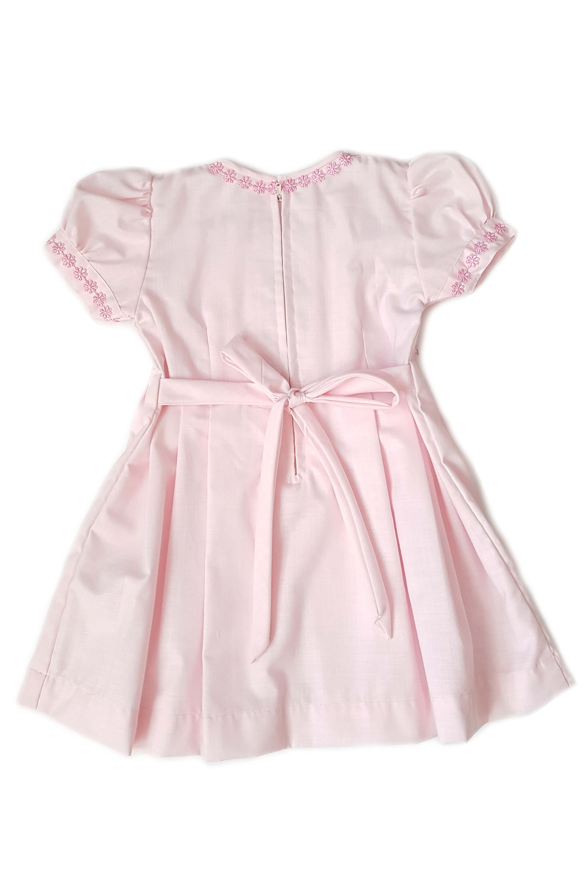 Back of pastel pink pleated dress with hand-embroidered rosettes along the bodice box pleats cascading down the dress with zippered back and sash to tie at waist for little girls as a bridesmaid's dress