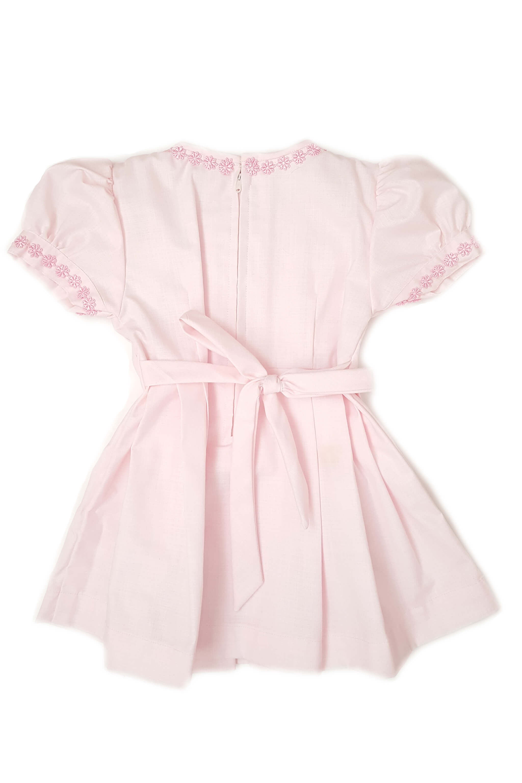 Back of pastel pink pleated dress with hand-embroidered rosettes along the bodice box pleats cascading down the dress with zippered back and sash to tie at waist for baby girls perfect for the bridal party