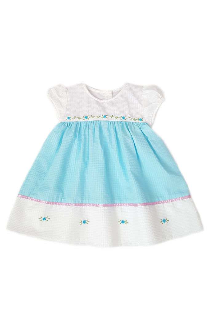 Classic seersucker dress in white with blue bodice and featuring hand-embroidered flowers and pink satin trim for baby girls