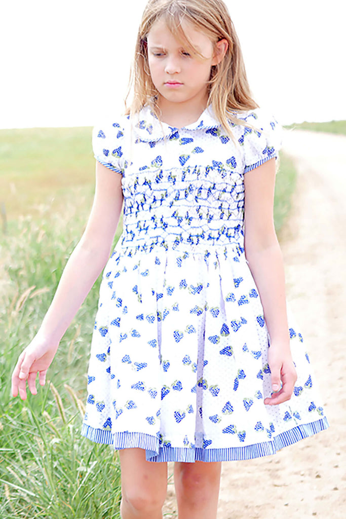 Girl walking on a dirt road beside a green field in a hand-smocked white dress with blue strawberries print