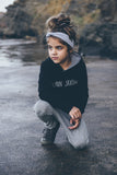 Black onyx Flynn Jaxon hoodie, with black and white striped hood lining, worn with light grey harem pants and grey headband