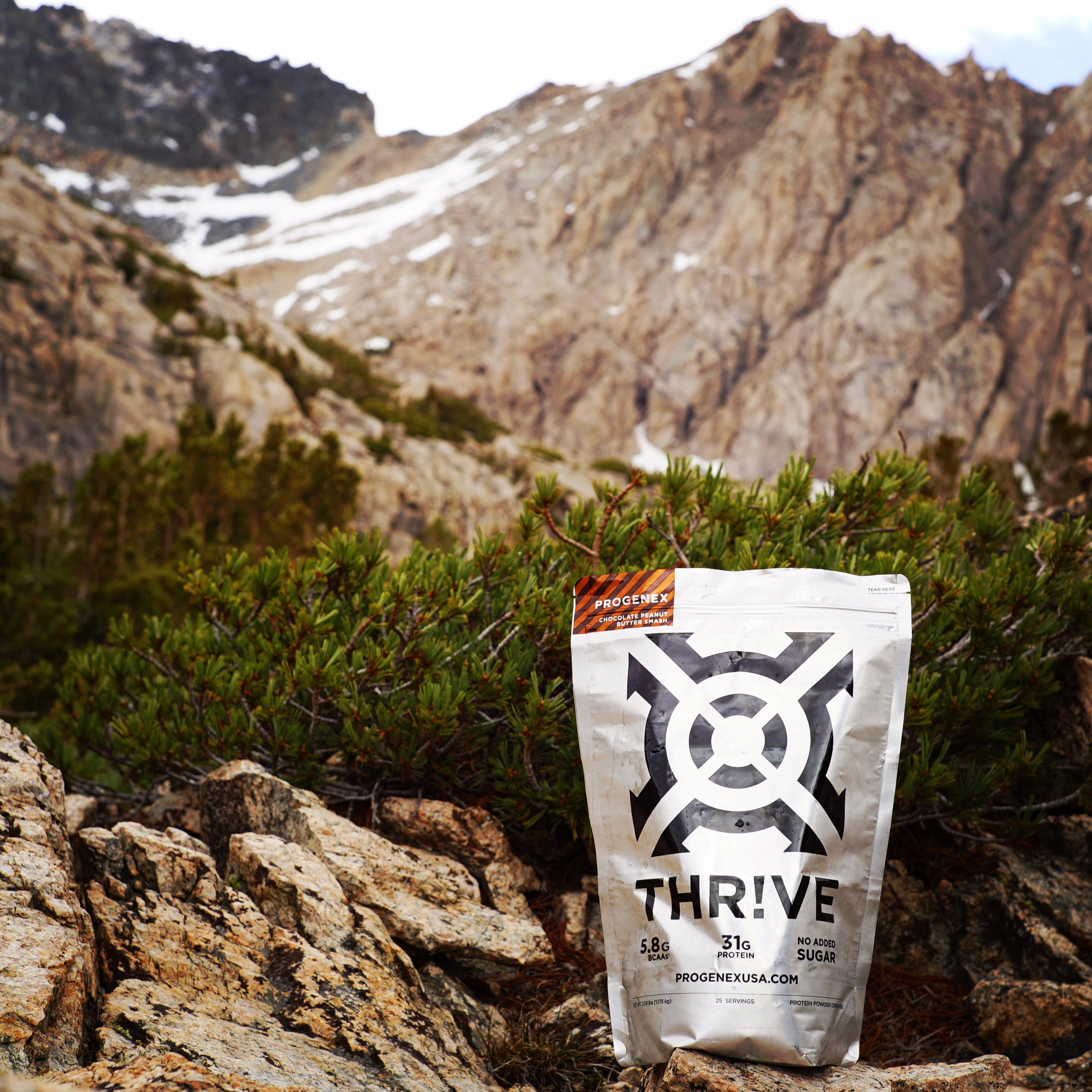 Bag of Progenex Thrive in front of a mountain.