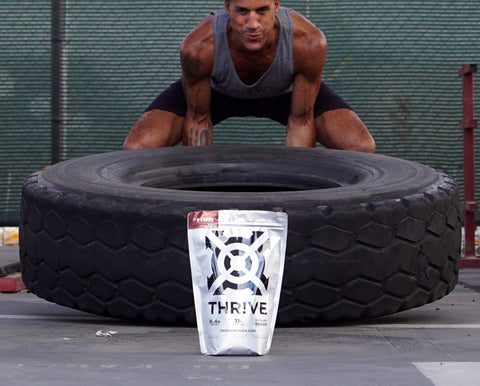 man flipping a tire behind a bag of Progenex Thrive