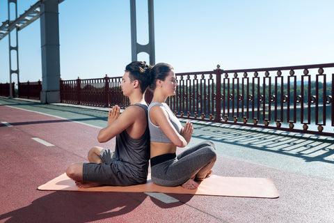 couple facing back to back sittting down breathing at hearts center pose