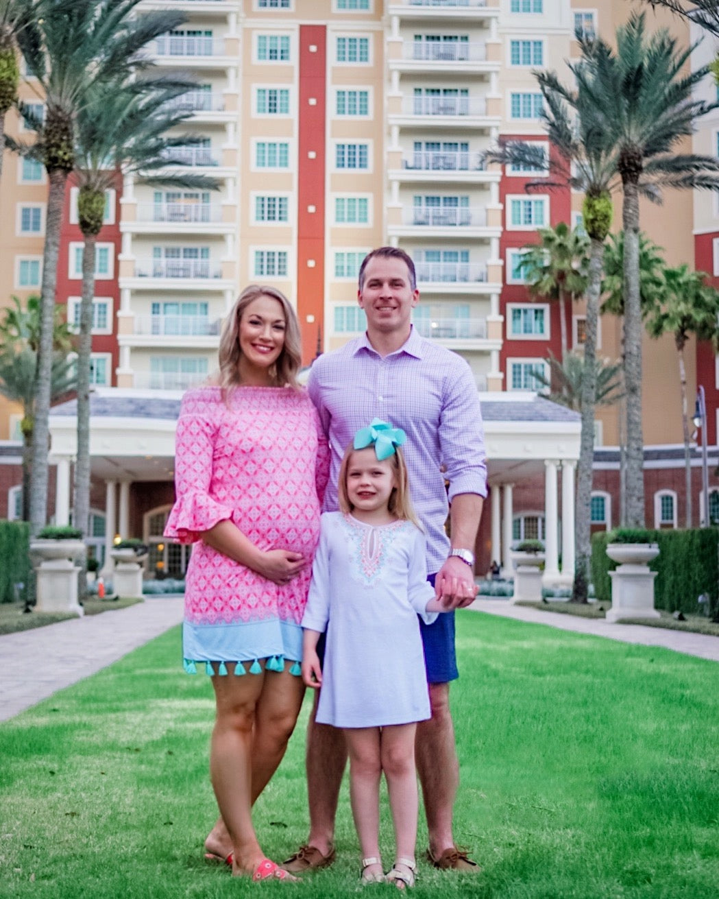 Family standing on lawn in front of Reunion Resort. Pregnant woman wearing Cabana Life Coral Tides Off The Shoulder Dress and girl wearing Cabana Life Aqua Citrus Embroidered Terry Cover Up.