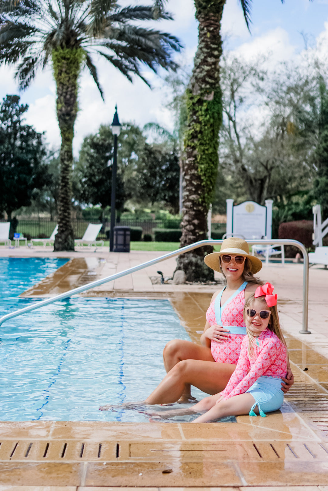 Mother and daughter sitting on edge of pool. Woman wearing Coral Tides Embroidered One-Piece and girl wearing Coral Tides Rashguard Swim Set