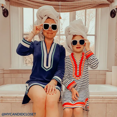 Woman wearing Navy/White Trim Terry Tunic with girl wearing Navy Geo Terry Cover Up sitting on side of bathtub wearing white sunglasses and towel headwraps