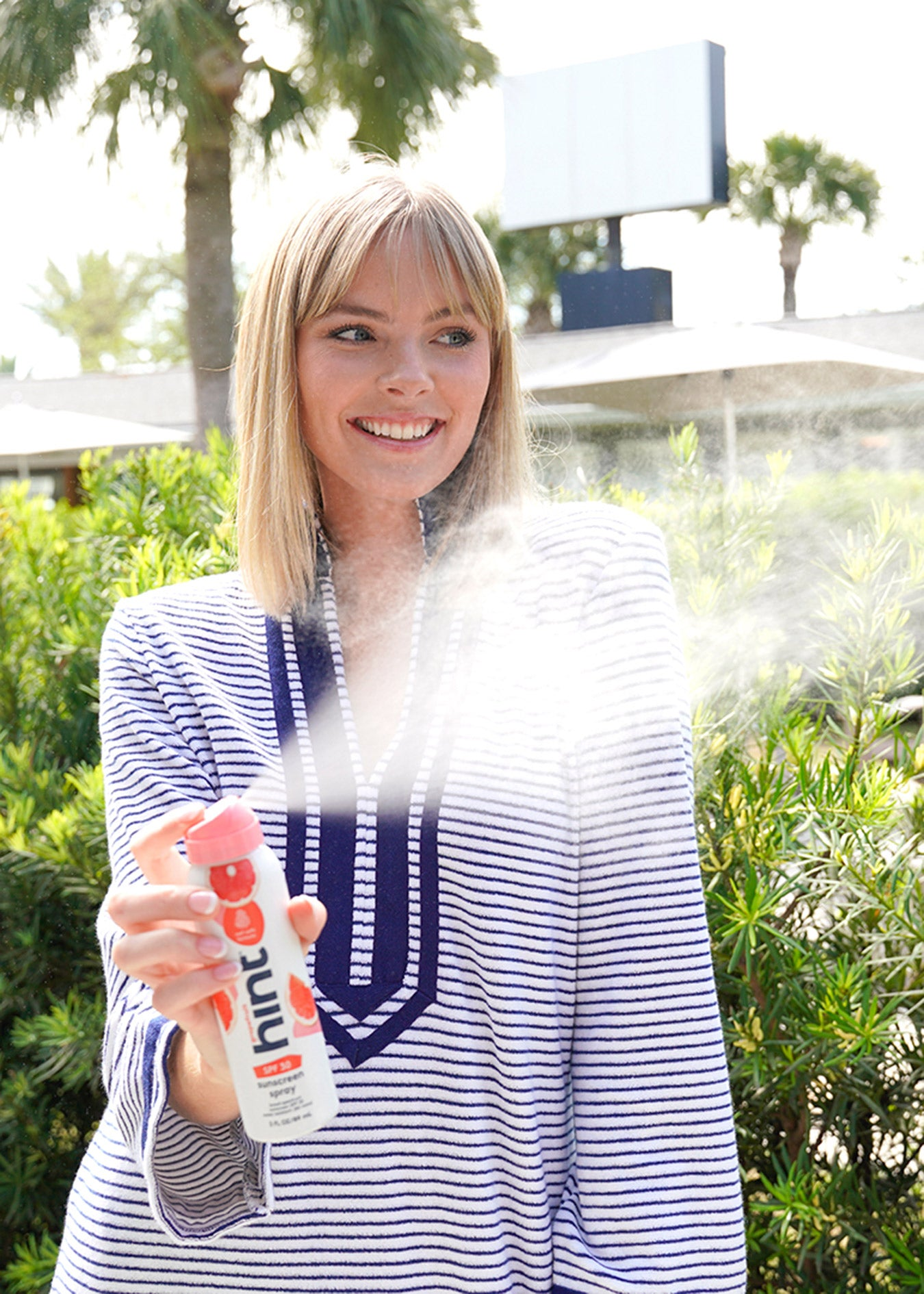 Woman wearing Navy Stripe Terry and spraying Hint sunscreen