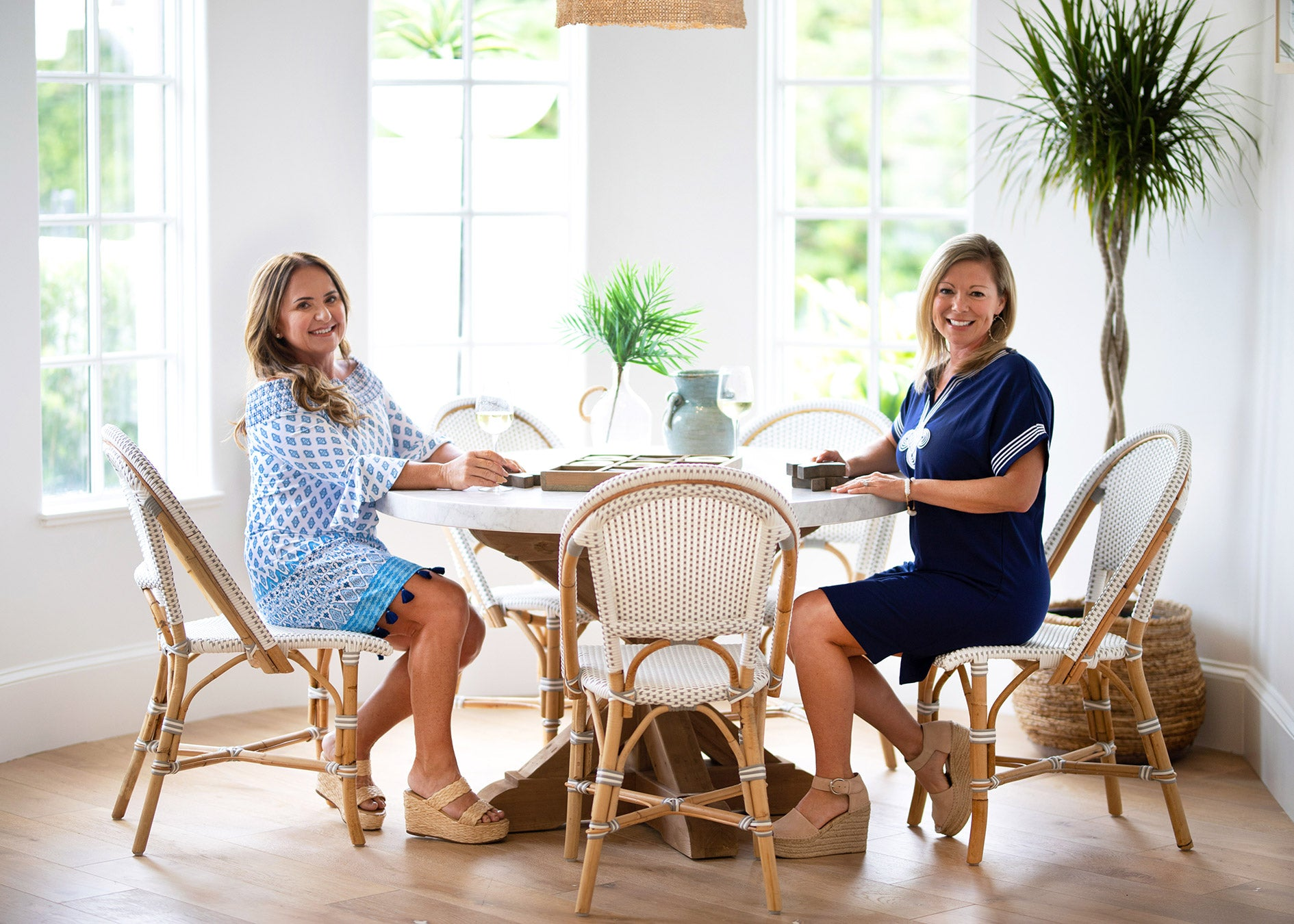 Two women sitting at table. Woman wearing Cabana Life Seascape Off the Shoulder Dress and woman wearing Navy Tee Dress