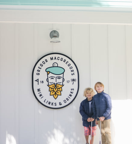 Two boys infront of Gregor Mcgregor's Mini Links & Drinks sign wearing Boy's Red Crab Swim Shorts and Rashguard set