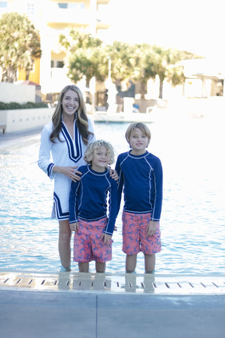 Woman wearing White/Navy Trim Terry Tunic and two boys wearing Red Crab Swim Shorts and Rashguard Set