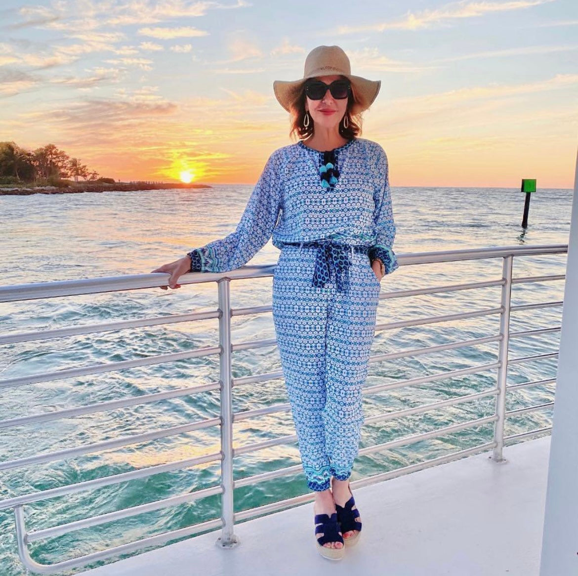 Woman standing at boat railing with sunset in background wearing Cabana Life Aruba Blues Tassel Blouse and Aruba Blues Beach Pants With Tie
