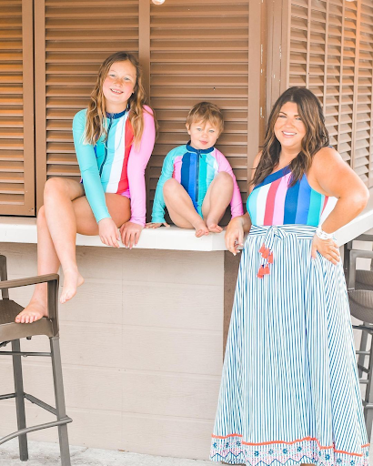 Two girls sitting on tiki bar wearing Cabana Stripes Unisuits and woman standing next to bar wearing Cabana Stripes One Shoulder One piece and St. Barts Embroidered Wrap Skirt