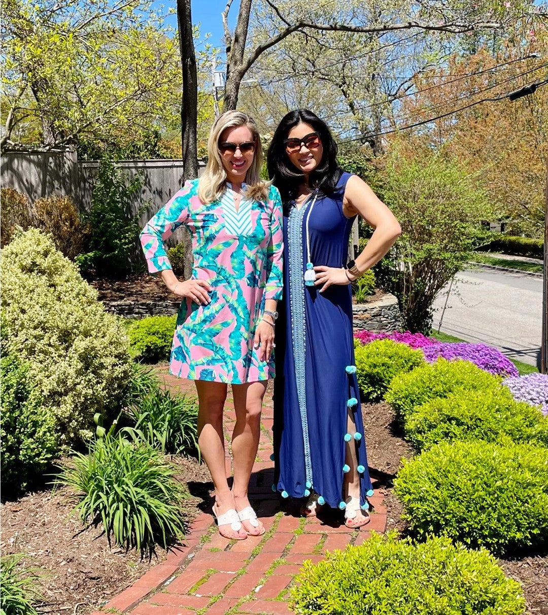 Two women standing in Garden wearing Cabana Life Preppy Palm Tunic Dress and Aruba Blues Embroidered Maxi Dress