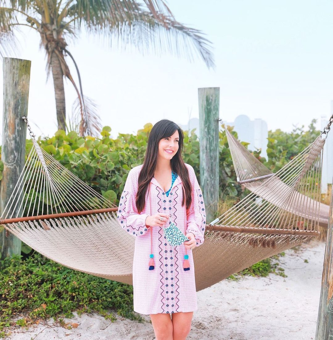 Woman wearing Cabana Life St. Barts Tassel Cover Up and holding Palm Desert Pleated Elastic Mask